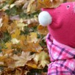Little baby girl in autumn leaves holding a yellow balloon — Stock Photo #31779855