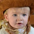 Portrait of a little boy in a cowboy hat and a light brown scarf — Stock Photo #41923531