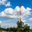Cell phone and communication towers against blue sky — Stock Photo