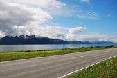 Asphalt road along the blue fjord. — Stock Photo
