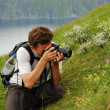 Man photographing flowers in the green slope of summer Soroya — Stock Photo