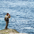 Man photographing against the blue sea — Stock Photo #32892599