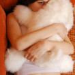 Teenage girl hugging with a cuddly toy in the sofa bed — Stock Photo