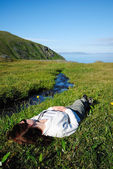 Woman lying supine near stream in green grass — Stock Photo