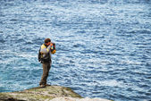 Man photographing against the blue sea — Stock Photo