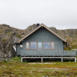 Norwegian wooden house on stilts under cliff — Stock fotografie