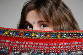 Caucasian woman behind the oriental shawl — Stock Photo