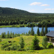 Wood house near blue lake in the middle of taiga forest. — Stock Photo