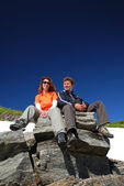 Couple of turists sitting on the rock — Stock Photo
