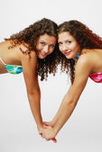 Close-up of pretty twins holding by the hands — Stockfoto
