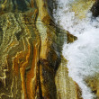 Close-up of riverbed through clear water flowing. — Stock Photo