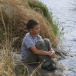 Boy sitting near the river — Stock Photo