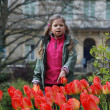 Girl behind the flower bed of red tulips — Стоковая фотография