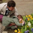 Happy man holding a child above the flower bed — Stock Photo #34255209