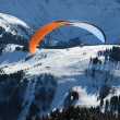 Stock Photo: Parachuter above the snowy slope in the Alps