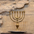 Menorah against ancient stone wall — Stock Photo #34919229