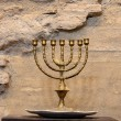 Menorah against the ancient stone wall — Stock Photo
