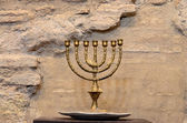 Menorah against the ancient stone wall — Foto Stock