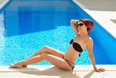 Woman sunbathing near the sunlit pool — Stock Photo