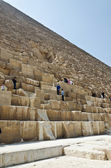Tourists clamberig on the ruined wall of an Egyptian pyramid — Stock Photo