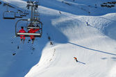 Skiers in a chair lift above the snow hill with skiing pistes. Cauterets ski resort. — Stockfoto