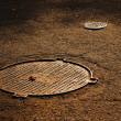 Sewer manholes on asphalt pavement — Stock Photo #38809605