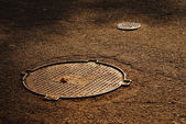 Sewer manholes on asphalt pavement — Stock Photo