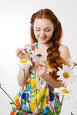 Red girl guessing by a camomile — Stock Photo