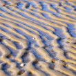Wavy pattern of wet sand on the beach. — Stock Photo