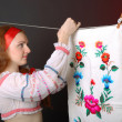 Ukrainian woman hanging the towel embroidered — Stock Photo