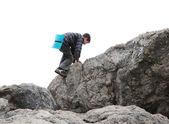 Teenage boy climbing up rocks — Stock Photo