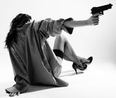 Undressed girl sits back and aims with handgun — Stock Photo