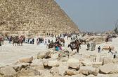 Tourists near famous Egyptian pyramids — Stock Photo