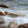 Blurred waves on wet stones of seacoast in off-season — Stock Photo