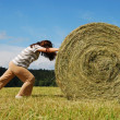 Woman pushing straw bale on — Stock Photo #39837753