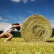 Woman pushing straw bale on — Stock Photo