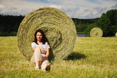 Woman resting under a straw bale — Stock Photo