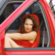 Close-up of a pretty woman in a red car — Stock Photo