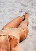 Tanned female body on the sand. — Zdjęcie stockowe