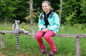 A girl near the tame lemur — Stock Photo