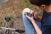 Boy with gadget near bike — Photo