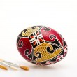 Colorful hand painted Easter egg and paint brushes — Stock Photo