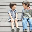 Little sibling sitting with smile — Stock Photo