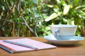 Cup of hot coffee withnotebook and pencil on table in the garden — Stock Photo