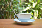 Cup of hot coffee on table in the garden — Stock Photo