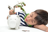 Little boy saving money in piggy bank money growing up as tree — Stock Photo