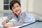 Little boy writing white paper on the floor — Stock Photo