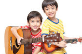 Little sibling boy playing guitar and ukulele happy face — Stock Photo