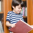 Boy in library holding book — Stock Photo