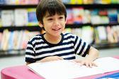 Little Boy in library reading book — Foto de Stock
